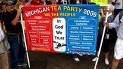 """A group from Michigan holds a banner comparing """"them"""" with """"us"""" and how """"American"""" each group's values are."""