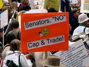 """A person in the crowd holds a sign advocating against emissions trading, otherwise known as """"cap and trade""""."""