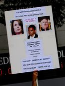 A man holds a sign indicating that the opposition is with President Obama's character rather than his race. It should be noted, however, that the photo of Obama smoking is a forgery, with the cigarette having been digitally added later.