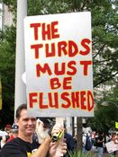 """A man holds a sign saying, """"The turds must be flushed""""."""