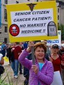 "A woman holds a sign reading, ""Senior citizen cancer patient: NO MARXIST MEDICINE!!"""