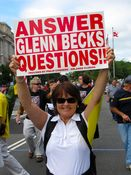 """A woman holds a sign saying, """"Answer Glenn Beck's Questions!"""" Note the lack of apostrophe in """"Beck's""""."""