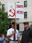 """A man holds a sign reading, """"Obamas Amerika"""". Note that the bottom of the sign is actually the back part of a rifle."""