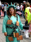 A woman wears a costume depicting the Statue of Liberty in chains.