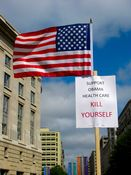 """A sign attached to an American flag assembly reads, """"Support Obama health care: Kill yourself""""."""