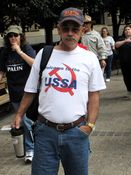 """A man wears a shirt depicting a hammer and sickle with the phrase, """"Welcome to the USSA""""."""