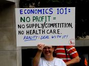A woman holds a sign discussing economics as it relates to health care.