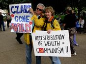 """A couple holds their protest signs. The man's sign says, """"Czars gone wild"""", while the woman's sign equates redistribution of wealth with communism."""