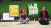 Two people sit on the sidewalk in front of the Capitol next to various protest signs.
