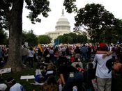 Crowd on the west lawn of the Capitol, with the Capitol dome visible in the background.
