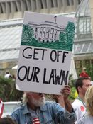 """A man holds a sign showing an image of the White House with the message, """"Get off our lawn""""."""