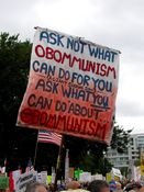 """Sign referring to Obama's economic plan as """"Obommunism"""", and referencing Ross Perot's """"giant sucking sound"""" comment."""