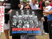 """A woman holds a sign saying, """"Stop the mob before it's all gone"""", depicting various politicians in Uncle Sam costumes and holding wads of money."""