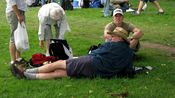 A man props himself up with an elbow while laying on the west lawn of the Capitol.