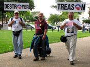 """Three men join the tea party rally from the north, with signs playing on the Obama """"O"""" logo. I consider the man in the maroon shirt in the center of the photo to bear a striking resemblance to G. Gordon Liddy (but I'm not implying that G. Gordon Liddy attended the event)."""