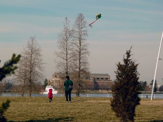 Meanwhile, a father and son take time to fly a kite...