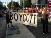"""On the sidewalk facing Jefferson Davis Highway, two people hold a sign reading """"BOYCOTT"""" to inform drivers of the action that is underway."""