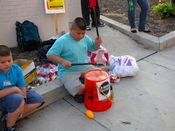 A child beats a makeshift drum with sticks on the sidewalk to the side of the main picket.