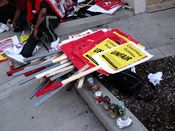 Signs stacked in a pile and noisemakers lined up in a row at the end of the picket.