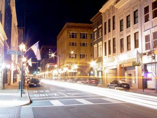 At street level, the lights bring the downtown alive as vehicles pass by and people enjoy the nightlife.