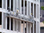 June 13, 2008: Crews in protective gear continue to work on the building's exterior, east side.