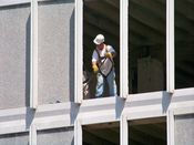 August 6, 2008: A worker uses a crowbar on part of the curtain wall on the building's seventh floor, west side.