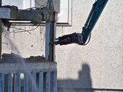 October 4, 2008: The long reach excavator prepares to crush a reinforced concrete column on the building's northeast corner at the second floor level.