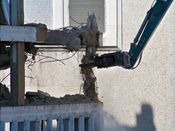 October 4, 2008: The long reach excavator completely crushes through the column, turning it to dust, while a water stream sprayed from below seeks to contain that dust.