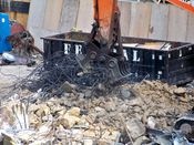 October 13, 2008: An excavator removes steel rebar from a pile of debris.