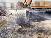 October 13, 2008: An excavator prepares to grab a large pile of steel rebar. Water is being sprayed on the pile to help contain dust.