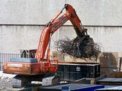 October 13, 2008: An excavator prepares to place a large pile of steel rebar into a dumpster.