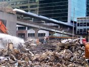 October 13, 2008: Workers walk near a pile of scrap metal and concrete debris. The skywalk over North Fort Myer Drive is visible in the background.