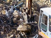 October 13, 2008: An excavator attempts to remove a tangled mass of rebar from the concrete.