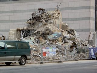 On the other side of the building, a pile of debris waits to be hauled off.