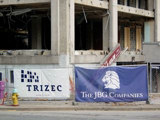 Along the perimeter fence hang banners for Trizec and The JBG Companies.